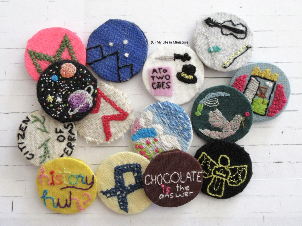About 15 embroidered pin badges are in a loose pile on a white background. Most of them relate to books like the Infernal Devices series, the Magnus Chase series, and Red, White and Royal Blue. At the bottom, the 'Chocolate is the answer' badge can be seen.