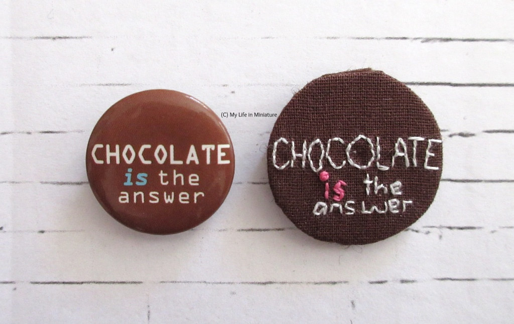 Two badges sit on a white background. They are both brown with 'Chocolate is the answer' written on in white text. The badge on the left is the one on the pencil case, and the one on the right is embroidered onto fabric.