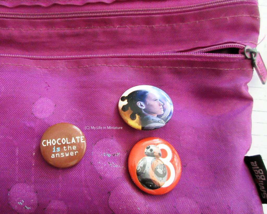 A purple pencil case sits on a white brick background. Two zips are visible at the top of the case, one open, and three pin badges are on the outside of the case. Two are Star Wars ones, one with Rey's profile and one with BB-8. The third badge is brown with 'Chocolate is the answer' in white text on it.