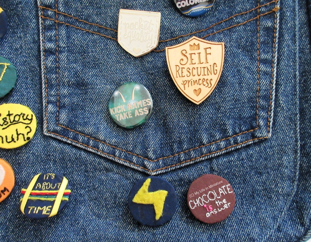 Image shows the front of a denim satchel bag. The bag has a number of pin badges on it, with one being the embroidered 'Chocolate is the answer' badge. Others include a wooden shield that says 'Self Rescuing Princess', and a white glittery pocket-shaped one that says 'Pocket Equality'.
