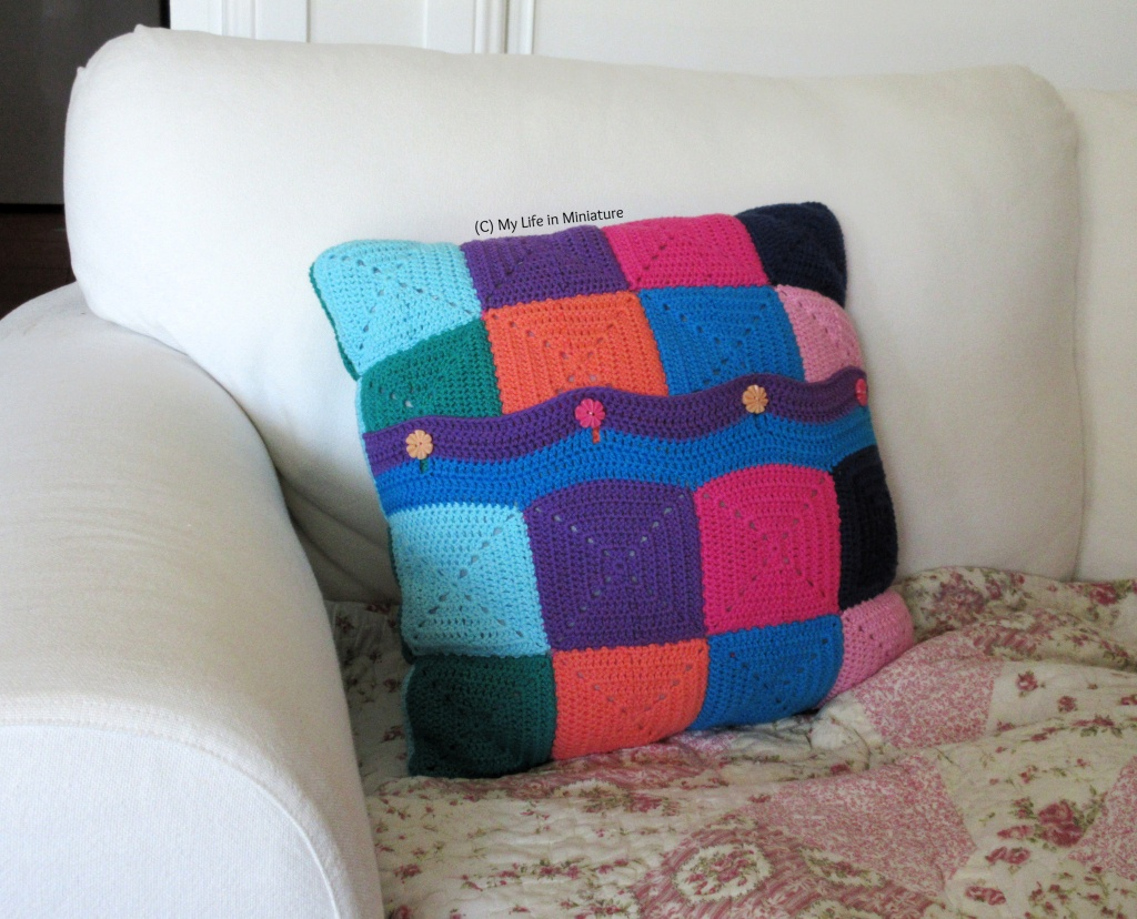 A crocheted cushion cover sits on a white couch. It is made of crocheted squares in various bright colours, with four buttons buttoned into a crocheted-on strip that covers the opening.