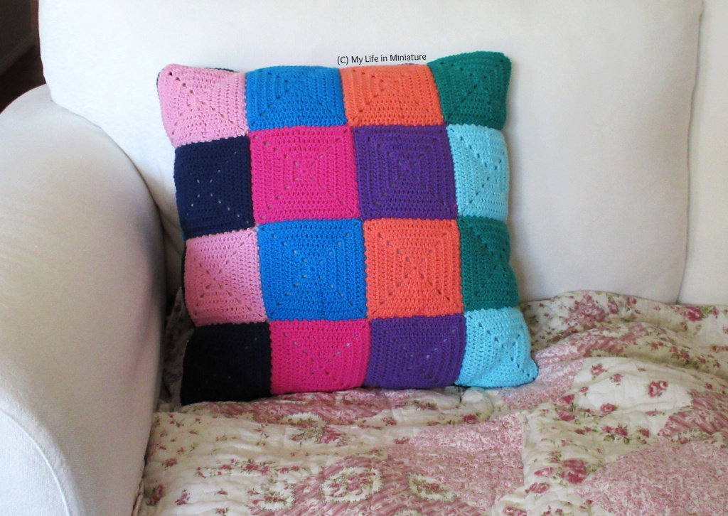 The back of the crocheted cushion cover sits on a white couch. There are no buttons or buttonhole additions to overlap any squares, so a grid of 4x4 squares is visible.