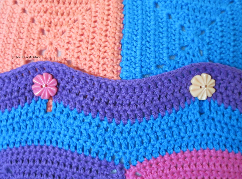 Close-up of two of the buttons on the cushion cover. The left button is dark pink, the right button is a pale peach. The crocheted overlap has buttonholes in it, and is striped blue and purple.