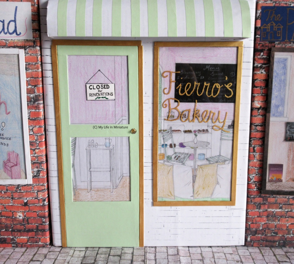 The storefront for Fierro's Bakery is pictured, in-between Needle and Thread and the Palace Library. The name of the bakery is painted on the window in gold, and a green door is to the left. Gold borders the door and window, and the store has a white brick background and a white-and-green striped awning across the top of the storefront.