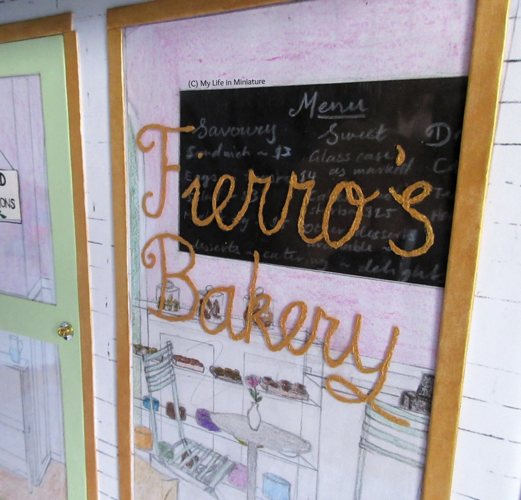 Close-up of the front window of Fierro's Bakery, and the painted name on the glass. It's painted in gold, and is a bit lumpy. Behind the glass is cushions in the foreground, leaning against the window like a bench seat. Further back is two pale green chairs around a silver table. Behind that is the counter, with glass case filled with sweets, and a chalkboard menu on the back wall.