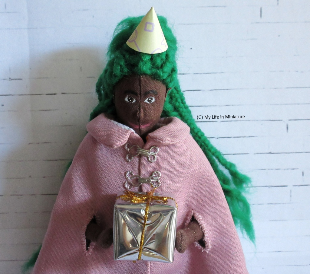 Hazel stands in front of a white brick background, holding a silver-wrapped present and wearing a conical party hat. She also wears a pale pink cape, and has her green braids down her back. She smiles down at the gift.