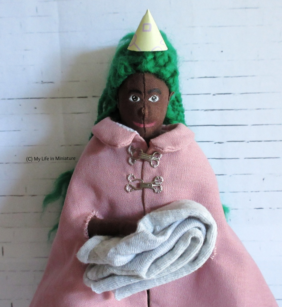 Hazel stands in front of a white brick background, holding a folded grey jersey garment. She smiles at the camera, and has on a party hat and a pink cloak.