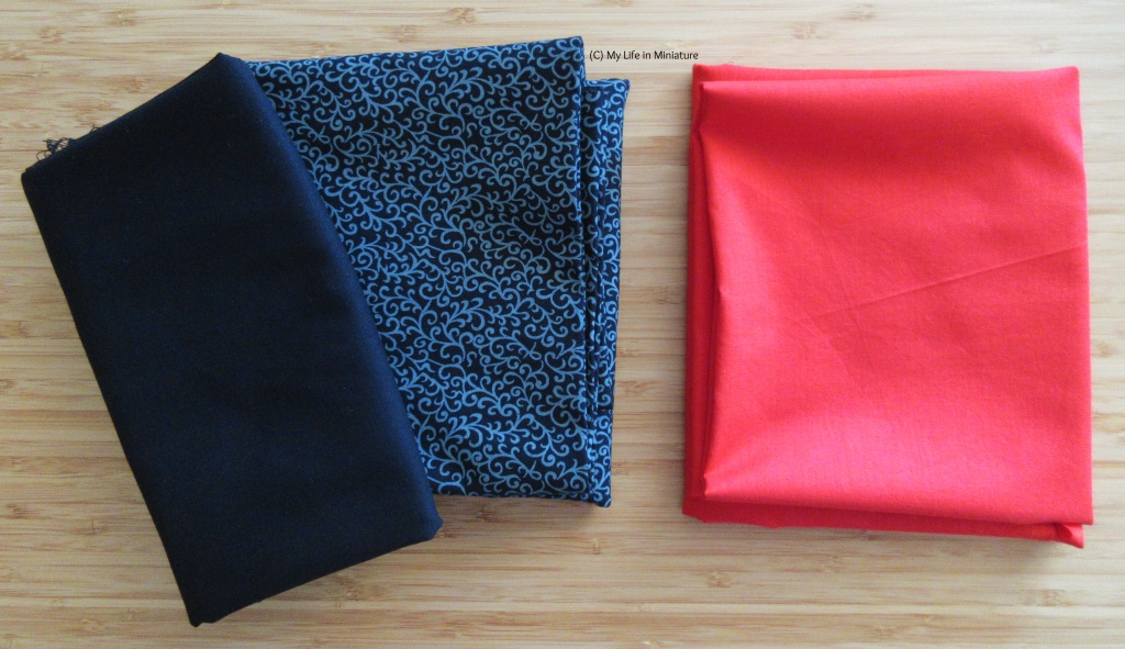 Three folded-up pieces of fabric sit on a wood background. The two on the left are stacked; the bottom one is black with a grey swirly paisley-esque pattern on, and the top one is plain black. The fabric on the right is bright red.