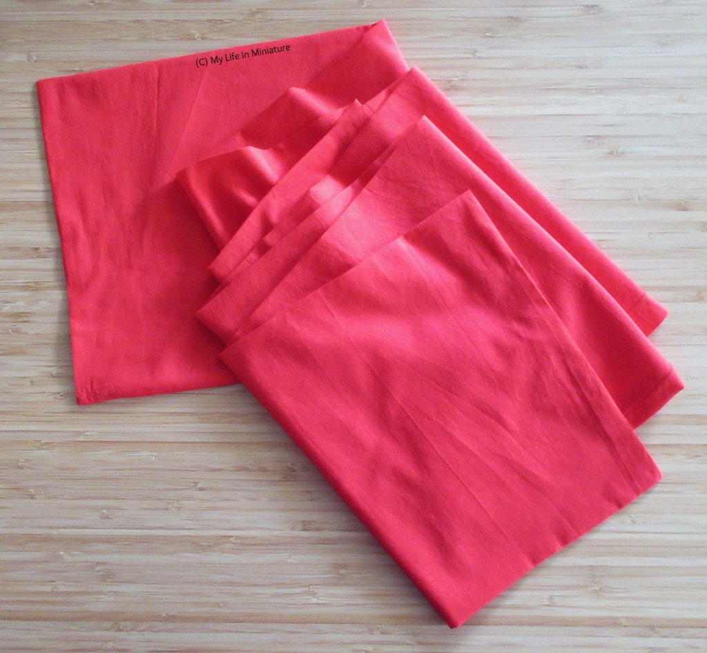 A long rectangular strip of bright red fabric sits, loosely folded accordion-style, on a wood background.