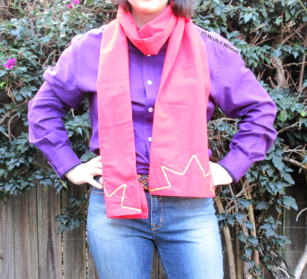 The author stands in front of a hedge wearing the red scarf around her neck, looped once with both ends in front of her. She also wears a purple button-down shirt tucked into jeans. She has her hands on her hips, and the two star motifs at the ends of the scarf are visible.