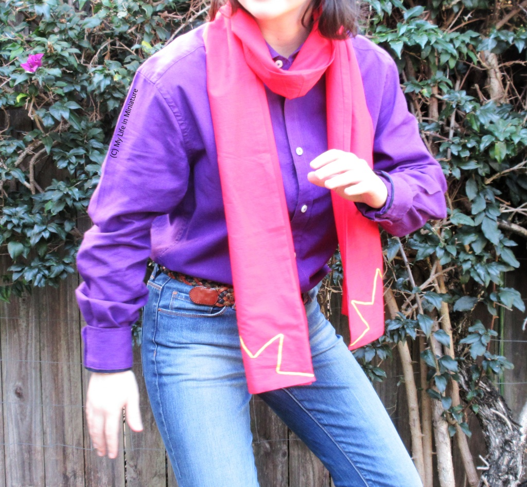 The author stands in front of a hedge, wearing the red scarf looped around her neck so both ends are in front. She also wears a purple button-down shirt tucked into jeans. She half-crouches and has one arm up, like she's heard a noise and is about to make a superhero's exit.
