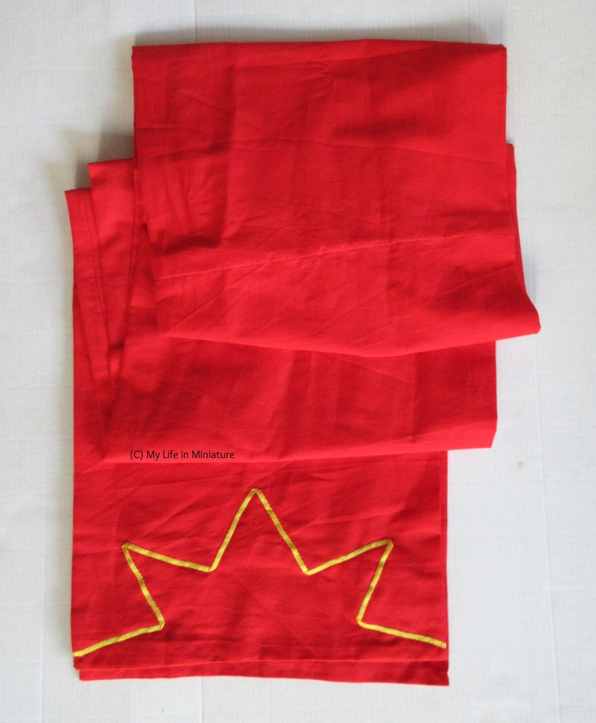A long red scarf, folded to fit into frame, sits on a white background. A length of yellow ribbon is sewn onto each end in a half-star shape.