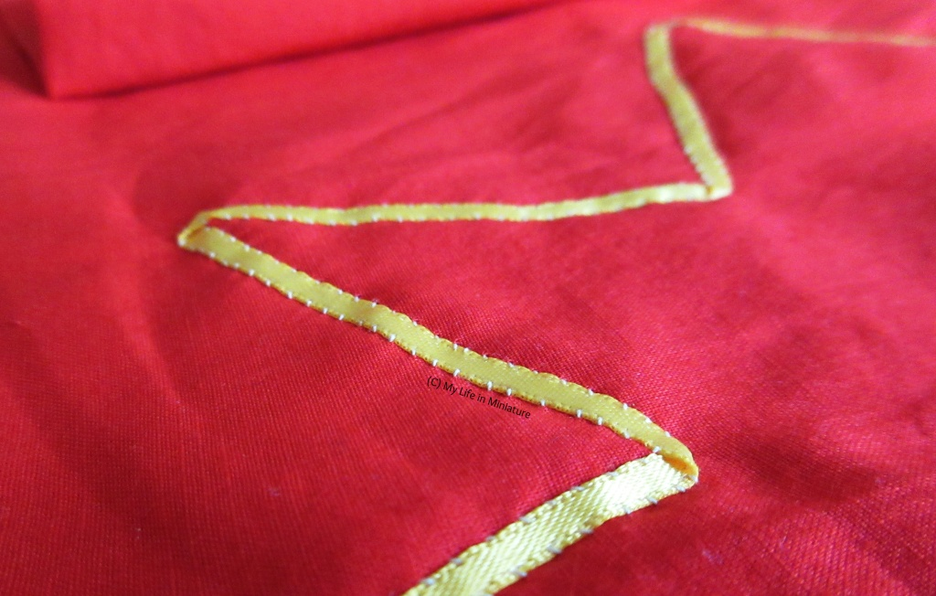 Close-up shot of the yellow ribbon sewn onto the ends of the scarf. The small stitches are visible, as well as the folds in the corners of the star shape.