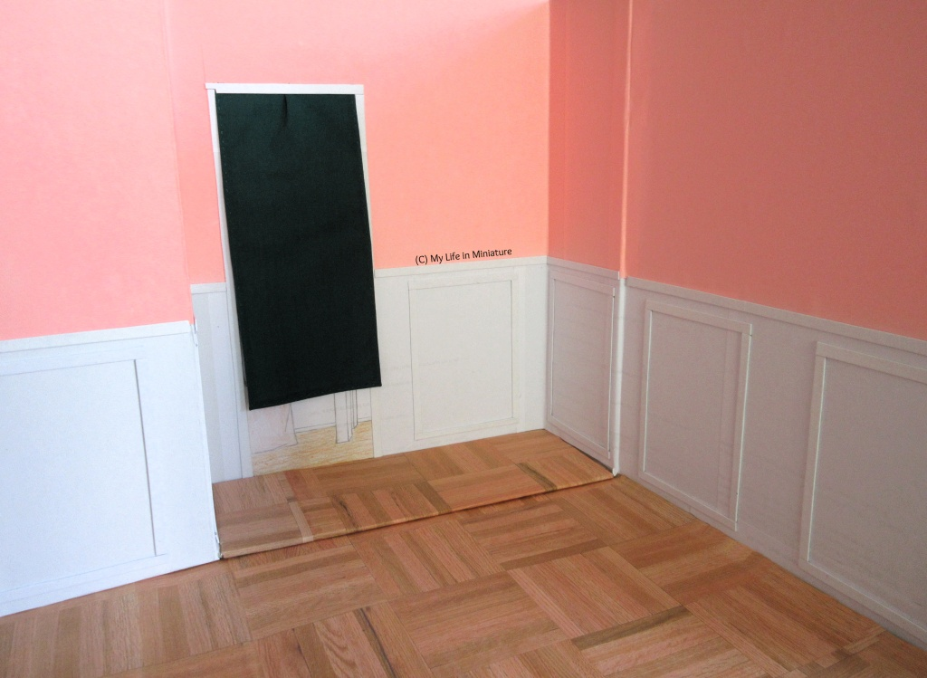 The interior of Fierro's Bakery. The upper two-third of the walls are pink, while the bottom third is white with raised rectangular panelling. There is a wood parquet floor, and a doorway in the wall furthest away, which is covered with a dark green curtain.