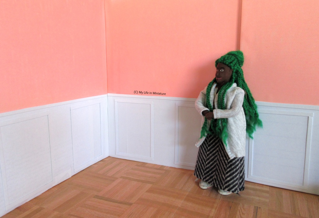 Hazel stands in a different area of the interior of Fierro's Bakery. She's dusting off her hands, wearing a wool skirt and grey cardigan. The top two-thirds of the walls are pale pink, and the bottom third is white with raised panelling. The floor is parquet wood.