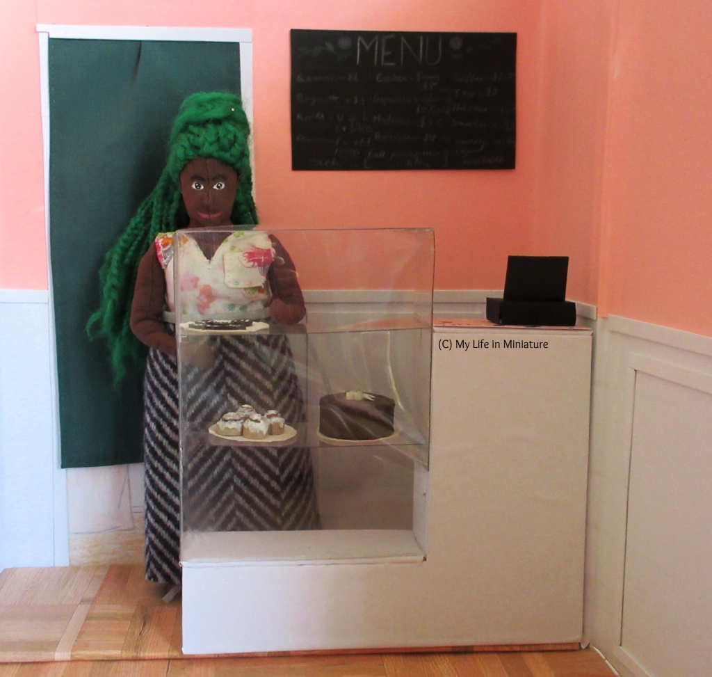 Hazel stands behind the front counter in Fierro's Bakery, putting a plate of dark chocolate chip cookies in the glass cabinet. She wears a floral shirt and a wool skirt. Behind her is a green-curtained door and a chalkboard menu on the wall.