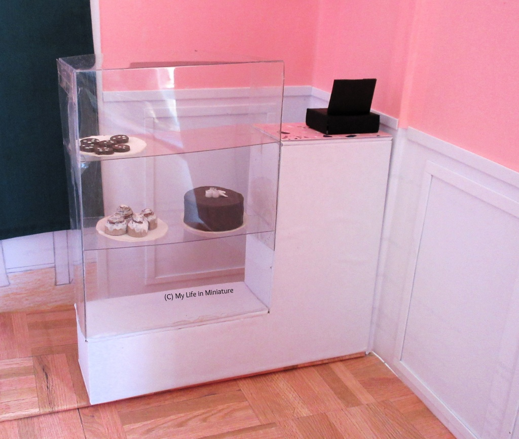 A better shot of the front counter on its own. It is white, with a small section on the right that has a black cash register on it. To the left is a clear glass box with three shelves for baked goods. On the middle shelf is a chocolate cake and a plate with four cinnamon rolls on. On the top shelf is a plate with dark chocolate chip cookies on.