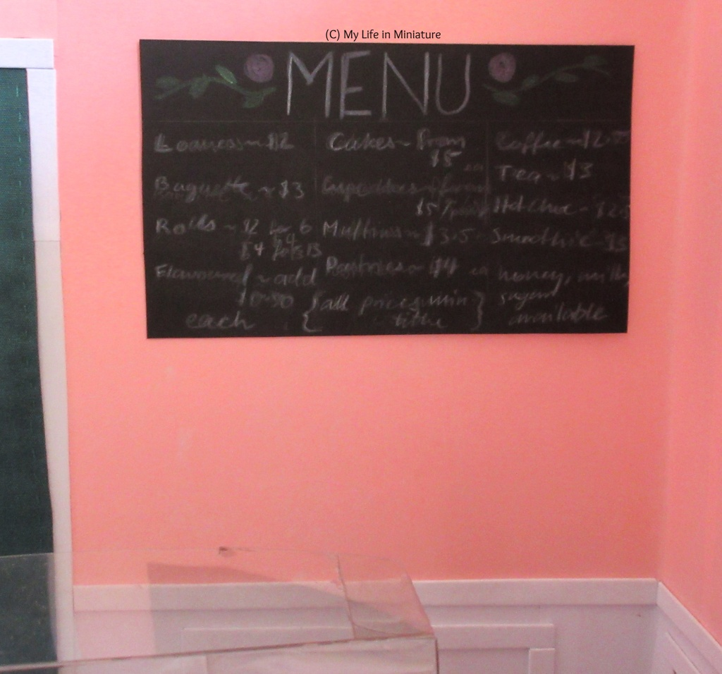 (slightly blurry, shh) image of the menu on the pink wall behind the counter and next to the green-curtained door. The word 'menu' is n all caps across the top, decorated with pink roses and green vines. The prices for various breads, sweet treats, and drinks is listed below in three columns.