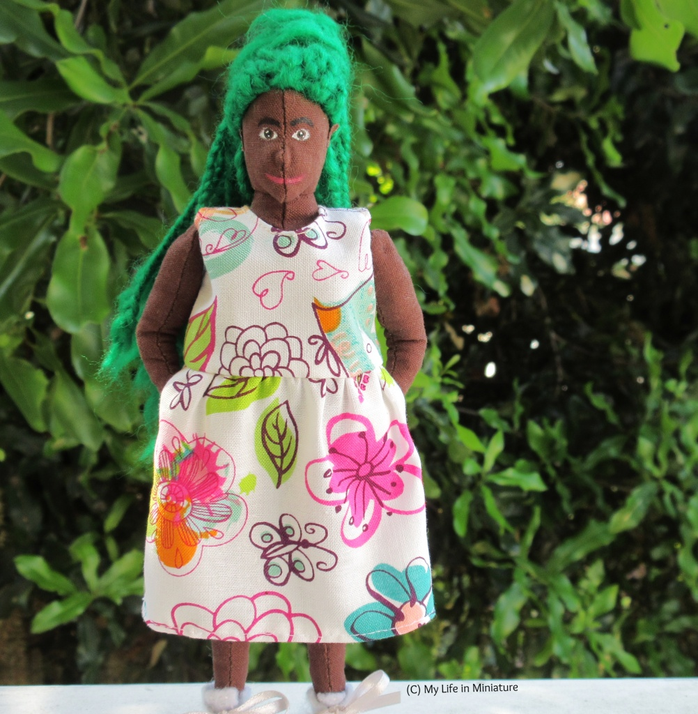 Hazel stands outside on a white wood surface against a dark green leafy bush. She faces the camera, smiling, with both hands in her dress's pockets. The dress is white with a multi-coloured floral print.