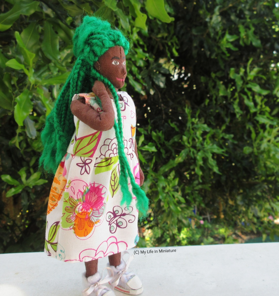 Hazel stands outside, in front of a green leafy bush on a white wood surface. She looks to the right, and is pulling a few of her braids forward over her shoulder. She wears the floral dress with white lace-up shoes.