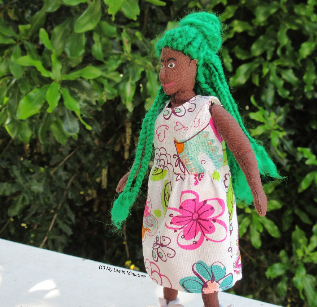Hazel stands in front of a green leafy bush on a white wood surface. She is facing left, captured in the motion of twirling on the spot to fan out the skirt of her dress, princess-style. Her braids swing with the motion, and her hands are out to the sides.