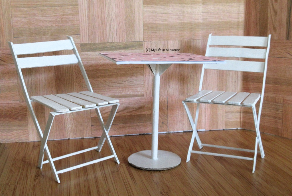 Two white chairs are tucked around a white square table, against a wood backdrop. The chairs look to be foldable café-style chairs, and the table is supported on a central circular dowel and a circular base. The table also has a pink top.