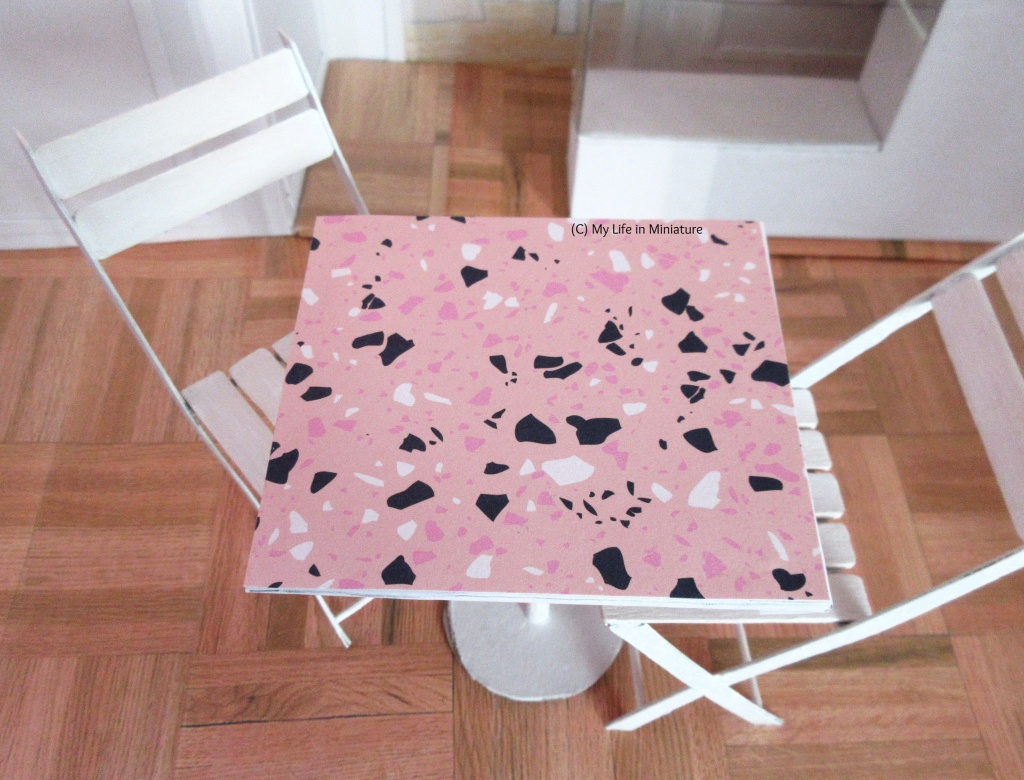 Close-up of the pink top of one of the café tables. It is pale pink, with terrazzo-esque shapes in black, white, and a darker pink scattered randomly. The two white chairs can also be seen, tucked under the table.