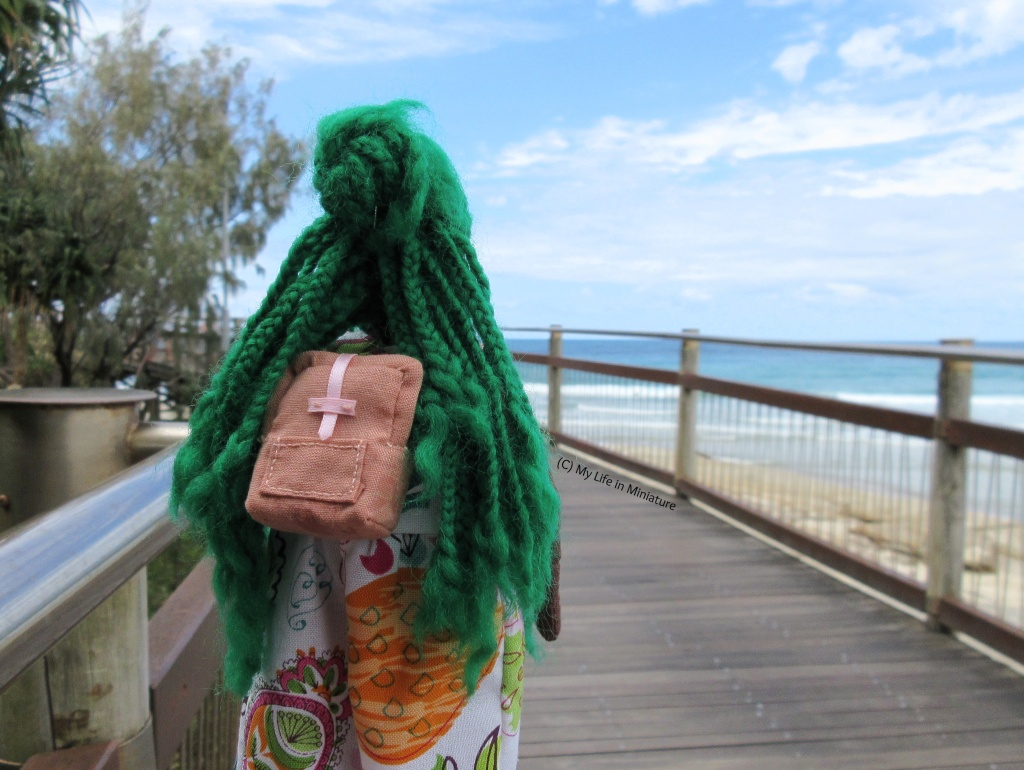 Hazel is photographed from the back, walking along a boardwalk. Beyond the railing is the beach, the sea, and the sky. The peach backpack is on Hazel's back, and her green braids are parted around it.