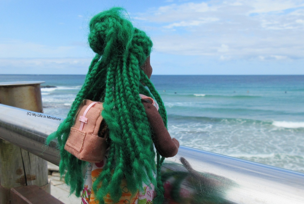 Hazel leans against the railing on the boardwalk, looking away from the camera towards the sea and sky. The backpack is on her back, visible through her parted braids.