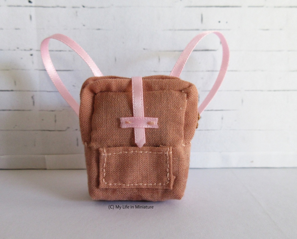 A small peach-coloured bag sits against a white brick background. The bag is visually similar to a Fjallraven Kanken bag, however it has pink straps and a pink opening on the front. There is also a small pocket on the front.