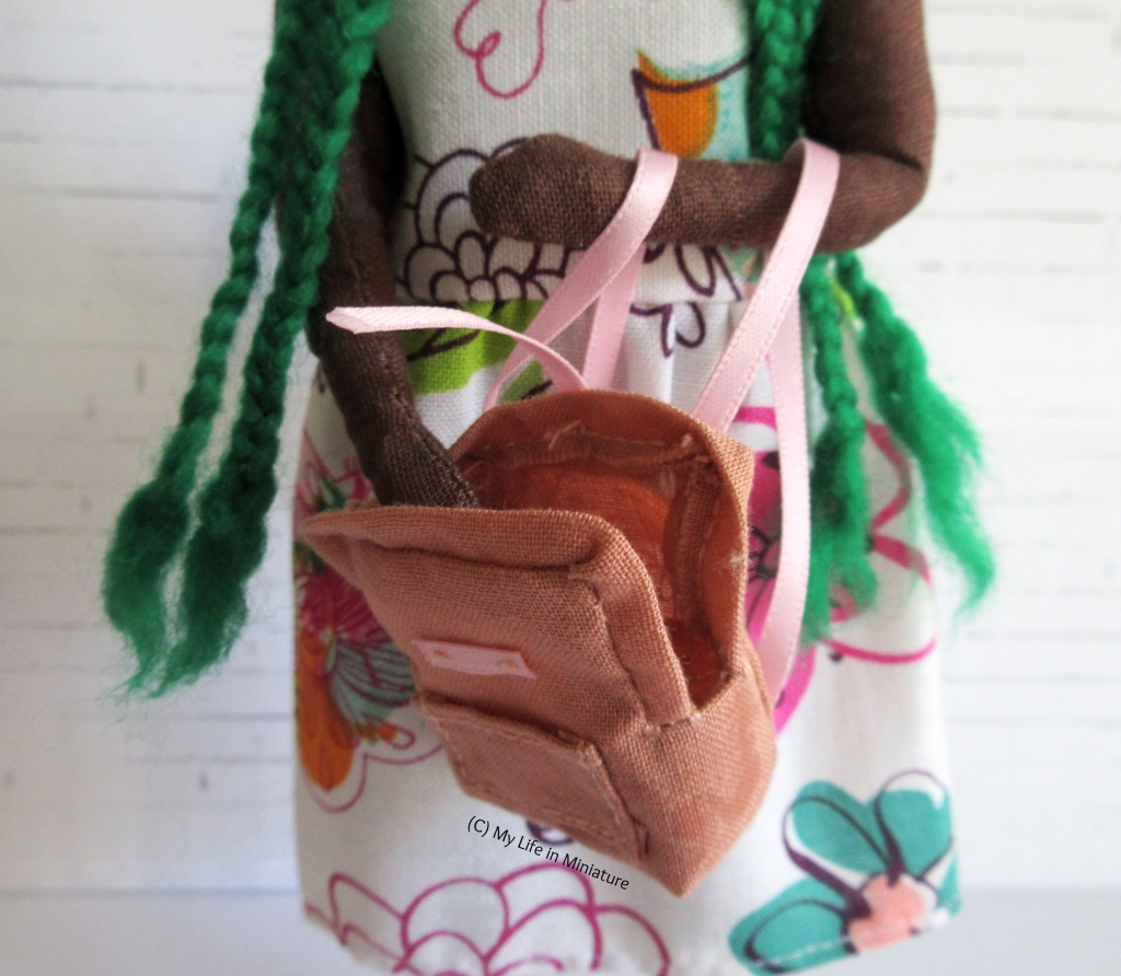 Hazel has the straps of the small peach bag looped around one arm. She has her other hand inside the bag, so that some of the inside of the bag is visible.