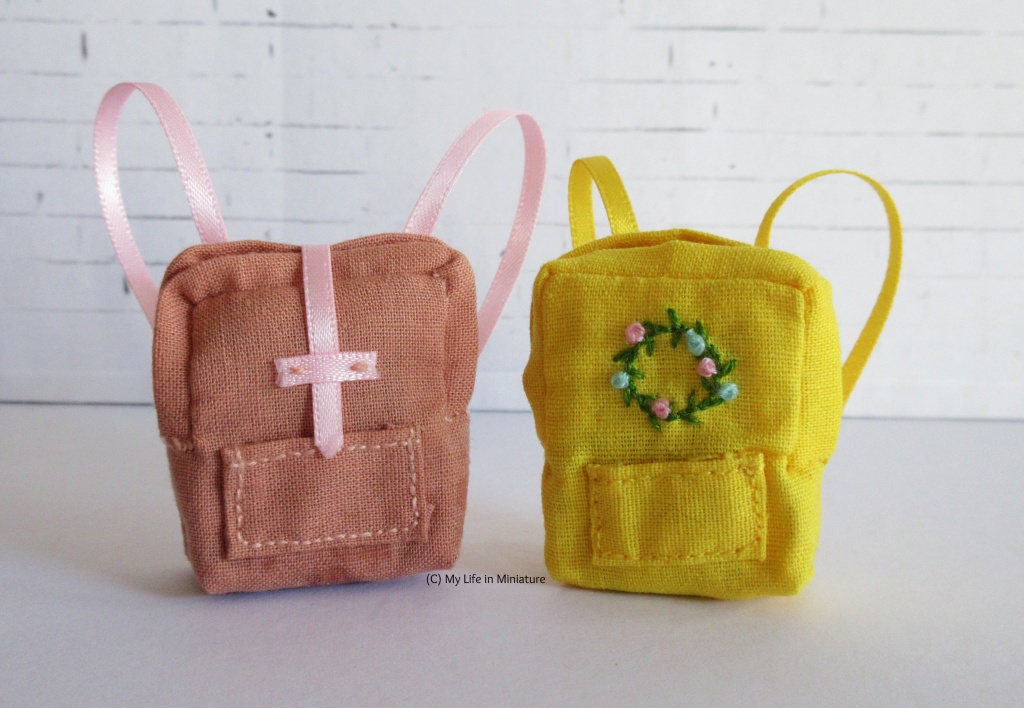 The small peach bag sits next to a very similar yellow bag against a white brick background. The yellow bag has shorter straps and an embroidered floral wreath on the front instead of a closure.