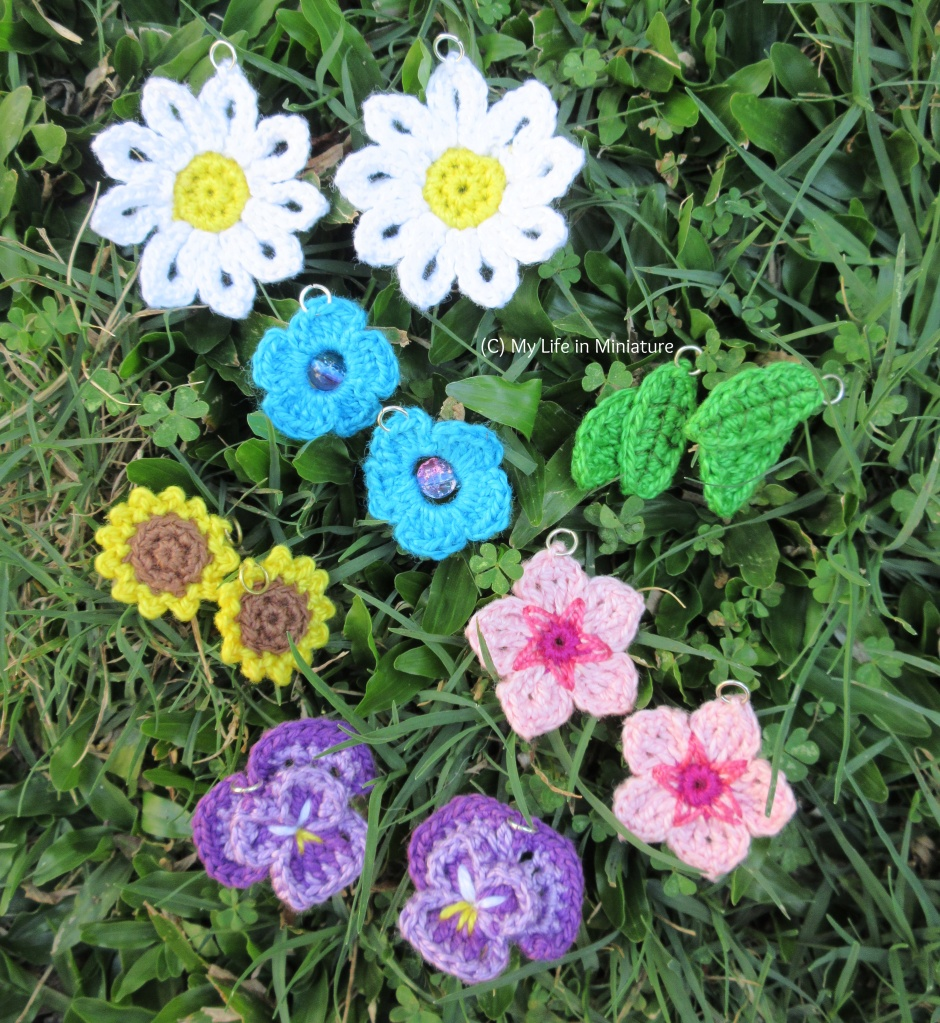 Six crochet earrings sit on grass. There are daisies, green leaves, blue flowers, sunflowers, cherry blossoms, and pansies, all in pairs.