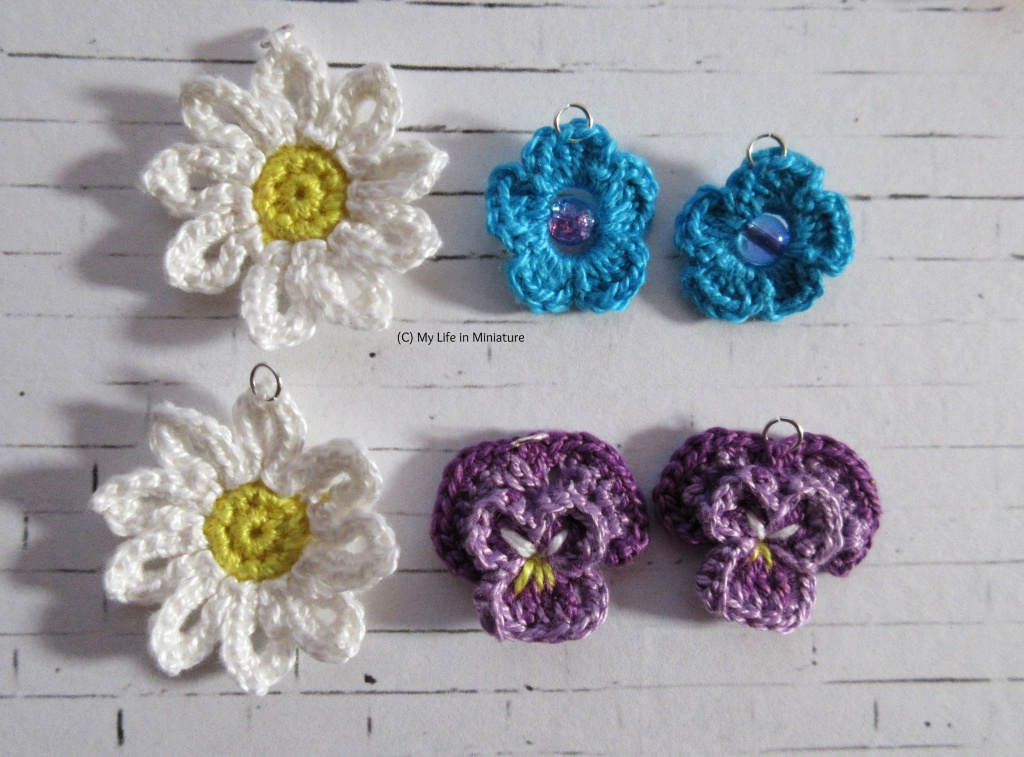 Three pairs of daisy, pansy, and blue flower earrings sit on a white brick background. Each has a small jump ring attached to the top.