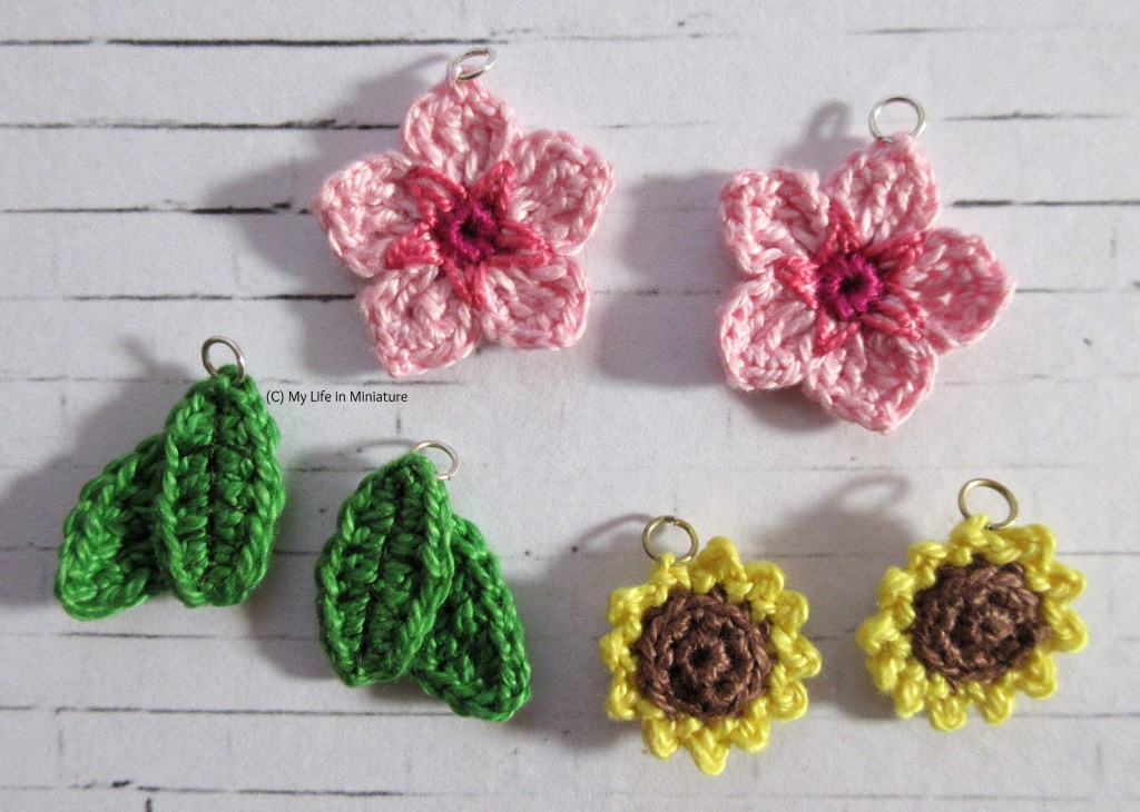 Three pairs of cherry blossom, green leaves, and sunflower earrings sit on a white brick background. Each has a jump ring attached to the top.